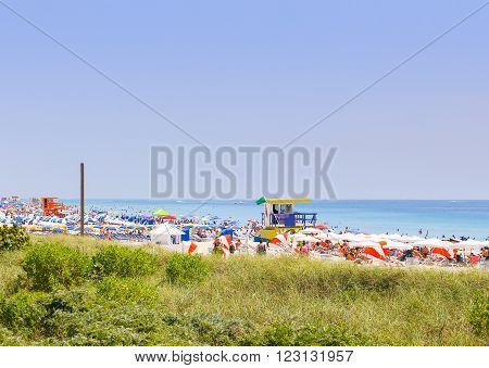 MIAMI BEACH, USA - MAY 9, 2015: Section of the beach with lifeguard stations and lots of colorful sunshades and beach chairs, in the front dunes with marram grass. People having fun in the sun.
