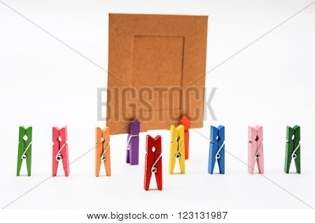 Red clothespin clothespins standing in front of a number followed by two clothespins holding orange blank