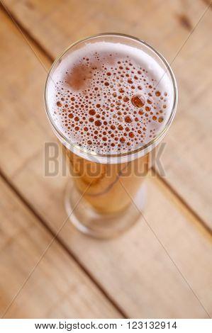 Pilsner vase glass with light lager beer on a grunge wood background