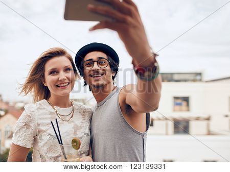 Two young friends taking self portrait with smart phone during a party. Young man and woman taking selfie at rooftop party.