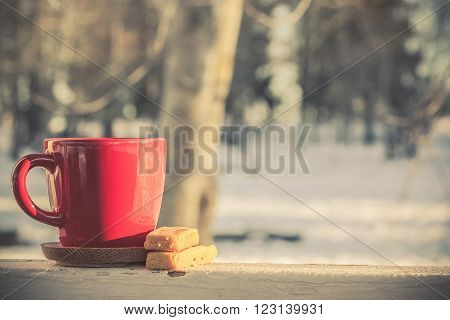 Red coffee tea mug cup with butter shortbread biscuits in winter morning glowing in yellow orange and pink colors sunny washed