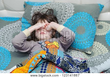 Girl in pajamas lying in bed and rubs his eyes