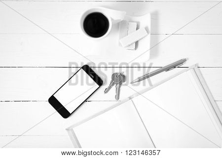 coffee cup with wafer phone key notebook on white wood background black and white color