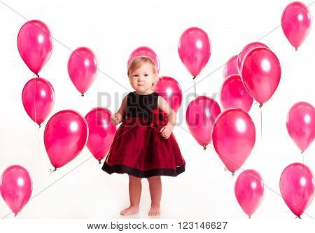 Cute baby girl 1-2 year old wearing stylish dress in room with balloons. Looking at camera. Childhood. Birthday party. Celebration.
