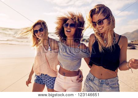 Group of beautiful young women strolling on a beach. Three friends walking on the beach and laughing on a summer day enjoying vacation.