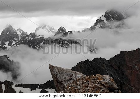 Landscape with Several Layers of Rocky Snowy Ridges mainly in Black and White Except Orange Rock on Foreground Overcast Clouds Sky poster