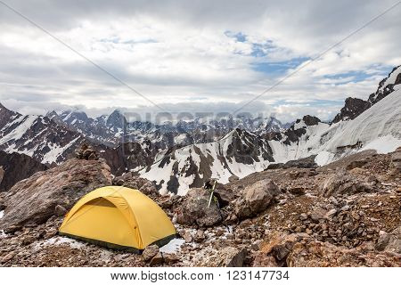 Small Alpine camping Tent located on rocky terrain stone surface and high mountain hills and peaks on background daylight cloud