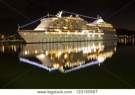 St. Johns Antigua - January 16 2016: Large luxury cruise ship Seven Seas Navigator of Regent Seven Seas Cruise lines illuminated standing in port at night lighting horizontal picture