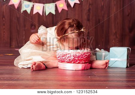 Baby girl 1 year old celebrating first birthday in room. Eating cake. Birthday decoration. Childhood.