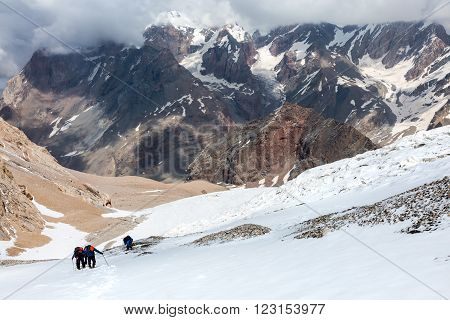 Group people approach high altitude mountain climbing camp heavy backpacks tons alpine gear walking Glacier Snowfield trail peaks snow sun sky stormy clouds background