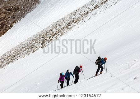 Members of Alpine Expedition Hardly Walking Up on Steep Snowfield Using Ice Climbing and Hiking Gear