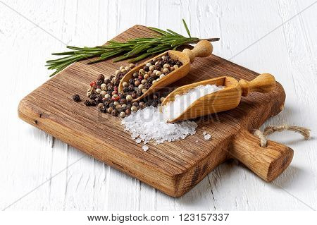 Salt pepper in wooden shovels and rosmarinus on wooden cutting board