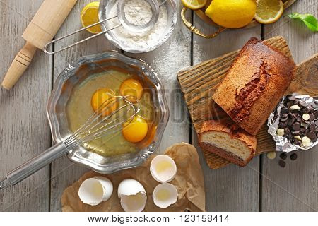 Composition of tasty cake with chocolate morsels and broken eggs on grey wooden background, top view
