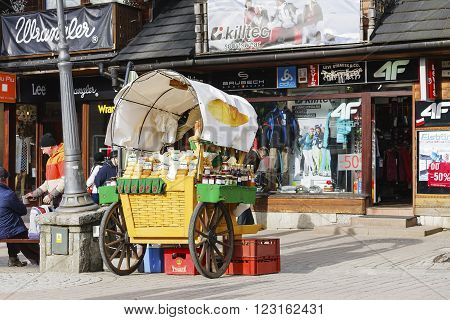 ZAKOPANE POLAND - MARCH 06 2016: Sales of Oscypek cheeses and other regional food products at Krupowki street since February 02 2007 oscypek is Polish regional product protected by EU law