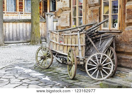 ZAKOPANE POLAND - MARCH 09 2016 Wooden waggon set against the wall of the building constructed in the traditional way with wooden logs. This scene reminds tradition of the region