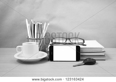 office desk : coffee and phone with car key eyeglasses stack of book pencil box black and white color