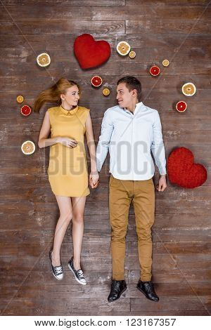 Top view creative photo of beautiful young couple on vintage brown wooden floor. Couple lying with hearts and citrus fruits