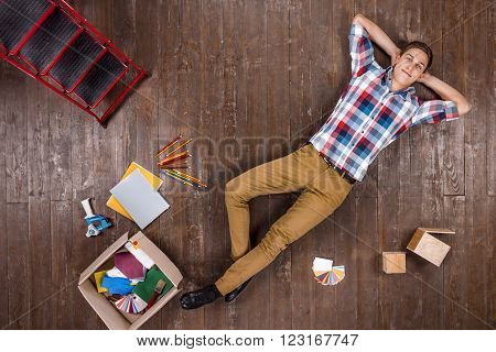Top view creative photo of handsome young man on vintage brown wooden floor. Man is ready for home renovation