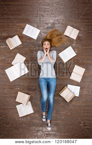 Top view creative photo of beautiful young woman on vintage brown wooden floor. Girl lying near books