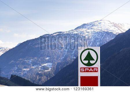 MATREI IN OSTTIROL, AUSTRIA - MARCH 28: Dutch multinational retail chain and franchise Spar logo with moutains in background on March 28, 2012 in Matrei in Osttirol, Austria.