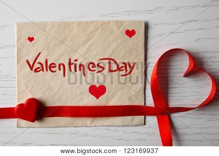 Blank present card with ribbon in form of heart on wooden background