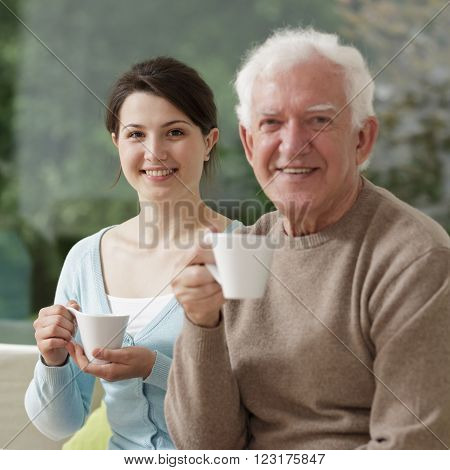 Young granddaughter and old grandfather sitting togheter