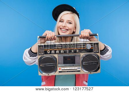Smiling young woman holding boom box over blue background