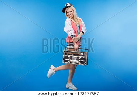 Full length portrait of a smiling woman holding retro boom box on blue background