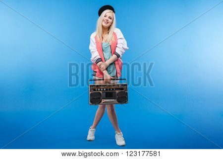 Full length portrait of a happy female teenager holding retro boom box on blue background