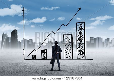 Picture of a young businesswoman wearing formal suit and look at a growing graph with upward arrow shot outdoors