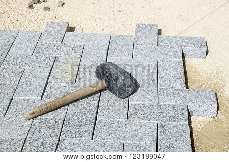 Old rubber mallet on a new granite pavement poster