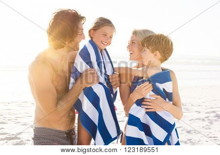 Wet son and daughter draped in towel embracing by parents after swim. Happy family at beach after swim in the tropical sea. Smiling father and mother drying children with a towels.
