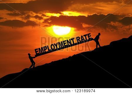 Silhouette of two workers carrying an employment rate text on the hill at sunset time