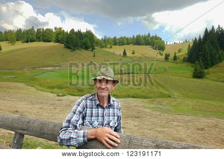 GARDA DE SUS, ROMANIA - AUGUST 04, 2015:  senior farmer is looking at me and is leaning your hand on wooden fence of countryside in Apuseni Mountains