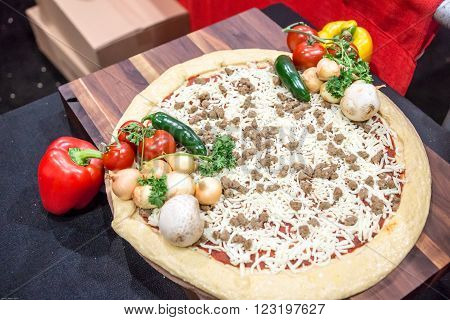 Gourmet pizza with onions and peppers ready for the oven