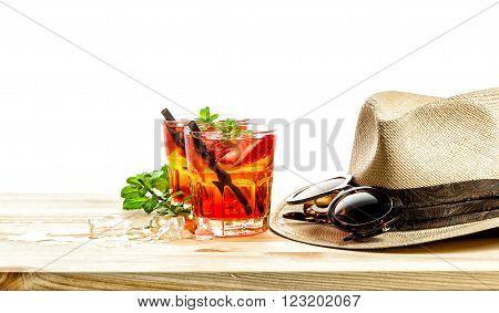 Red tropical drink. Campari aperol caipirinha sangria. Holidays concept with sunglasses and straw hat