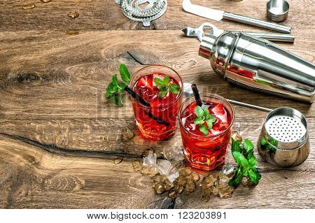 Red cocktail with ice mint leaves and strawberry. Campari aperol caipirinha mojito soda water drink