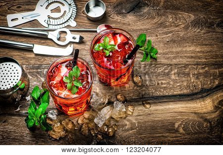 Red drink with ice mint leaves and strawberry. Cocktail campari aperol caipirinha mojito soda water. Dark toned picture