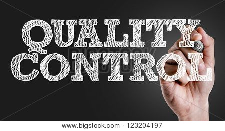 Hand writing the text: Quality Control