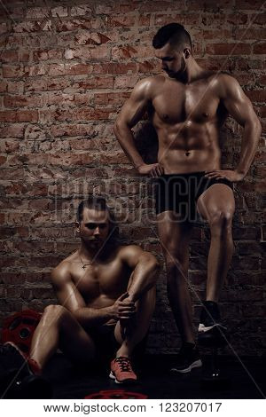Young muscular men near red brick wall