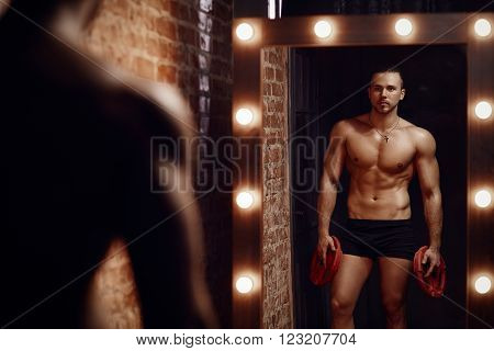 Young muscular man holding plates looks into mirror