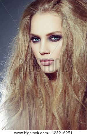 Vintage style portrait of young beautiful woman with long hair and smoky eyes make-up