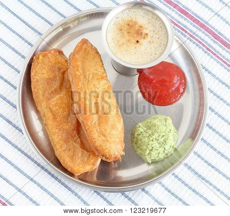 Indian food raw banana fritter, which is a traditional and popular dish, made from dipping slices of raw banana in chickpea flour batter and deep-frying them, with coconut chutney and tomato ketchup.