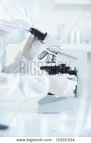 Scientist In Sterile Environment With Microscope