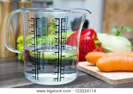 1/2 Liter / 500Ml / 5Dl Of Water In A Measuring Cup On A Kitchen Counter With Vegetables
