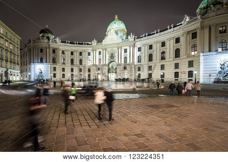 Hofburg Palace in centre of Vienna. Official residence and workplace of Austria President. Night scene with tourists walking near building. Europe travel.
