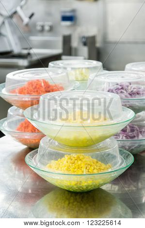 Vegetables prepped for salads or salad bars covered in a commercial kitchen