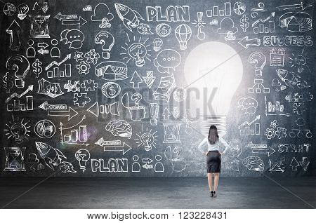 Businesswoman standing in front of blackboard with many business icons big light bulb in front. Back view. Concept of having new idea.