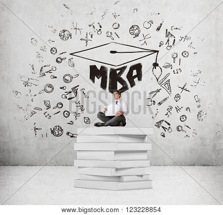 Businessman with laptop sitting on pile of book MBA and science icons around. Concrete background. Concept of studying.