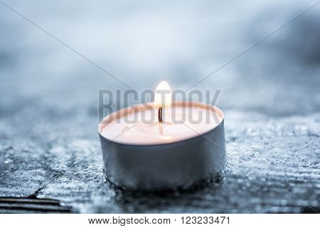 Romantic Winter Tealight On Cracked Ice Above A Wooden Floorboard